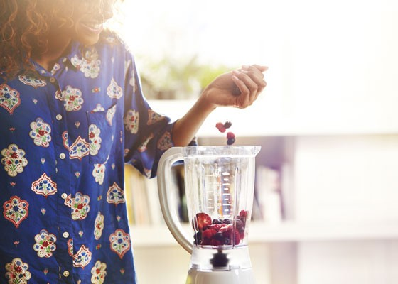Woman adding fruit to blender